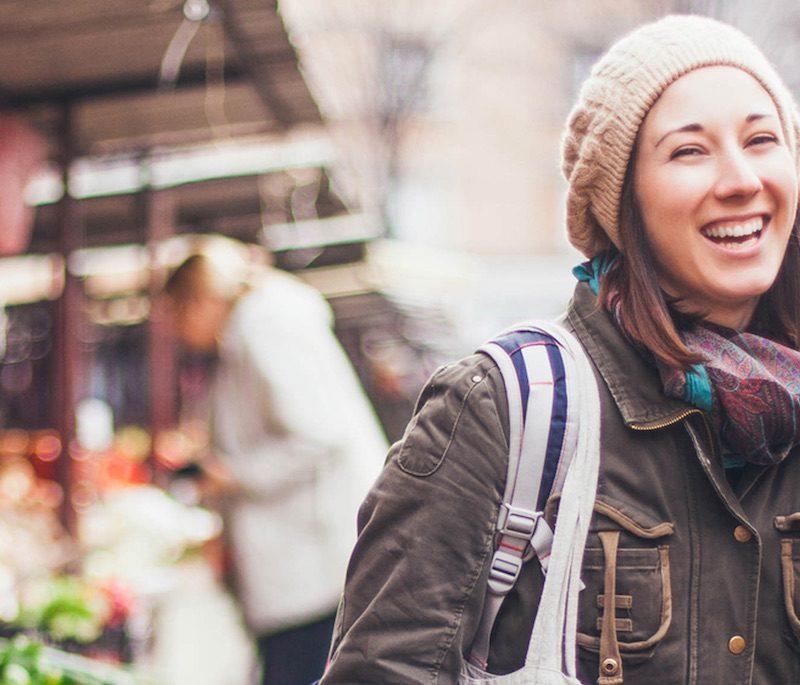 Eine junge Dame läuft fröhlich über einen Markt