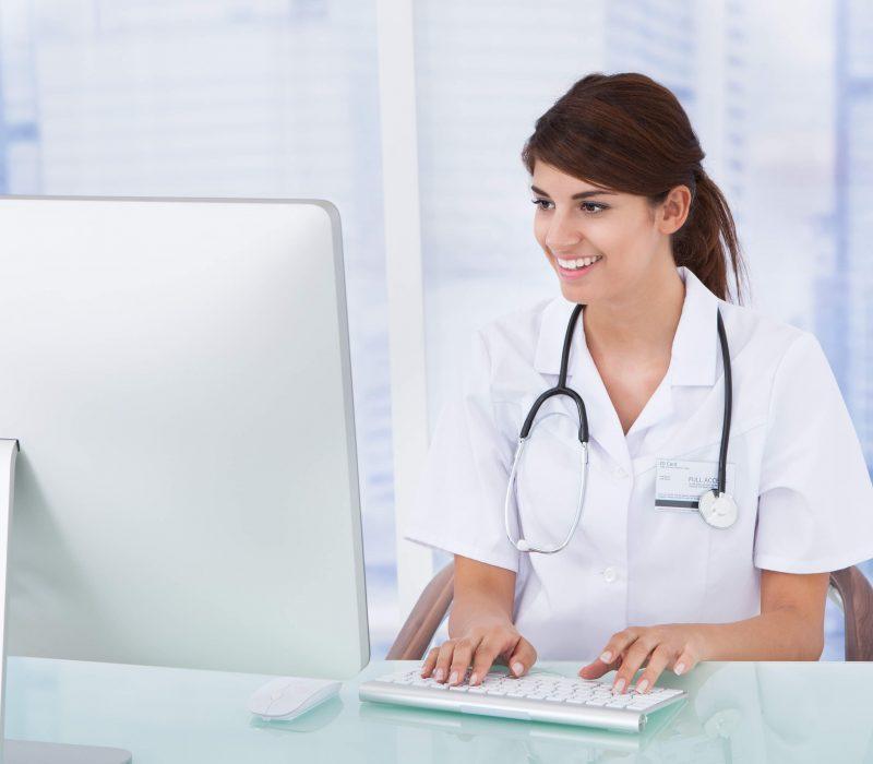 Krankenschwester sitzt am Schreibtisch